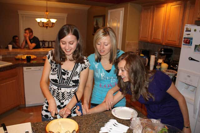 Natasha and two other women standing around a cake that Natasha is cutting