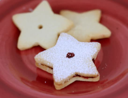 Three shortbread cookies with raspberry preserves on a red plate