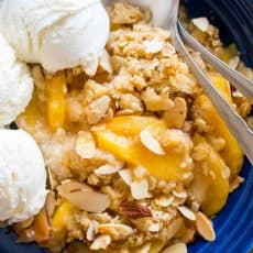 This Peach Crisp is our favorite summer peach recipe. The peach juices bubbling under the crisp buttery crunchy topping is completely irresistible. Add a generous dollop of vanilla ice cream! | natashaskitchen.com