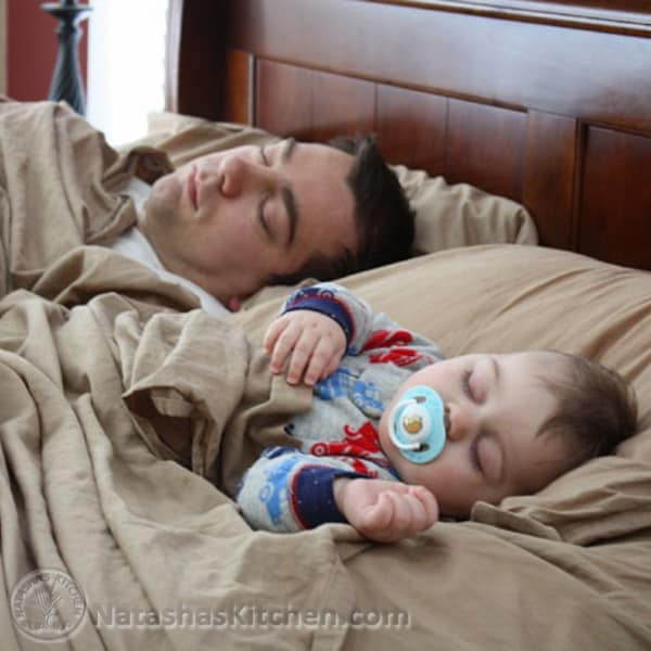 A father and baby son sleeping in bed