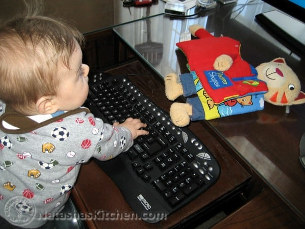 A baby sitting on the keyboard of a computer