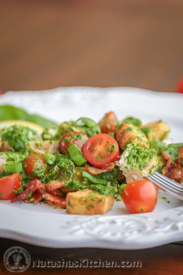 A plate with creamy spinach salad with chicken and baby tomatoes