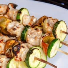 Grilled garlic chicken skewers on a white plate