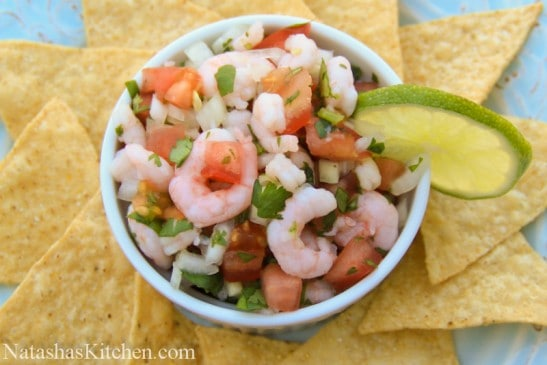 A bowl with shrimp pico de gallo garnished with lime and chips around the bowl