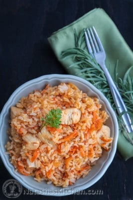 A bowl of Ukrainian chicken plov, rice pilaf, with a green cloth napkin and fork beside the bowl