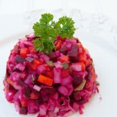 Russian vinaigrette salad with beets and sauerkraut on a white plate