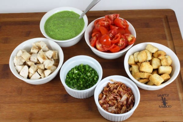 Ingredients in white bowls for creamy spinach salad with chicken and baby tomatoes