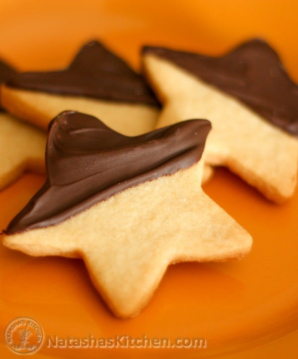 Four chocolate shortbread cookies on an orange plate