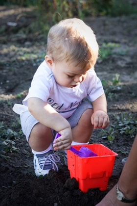 A little boy shoveling soil into a plastic bucket