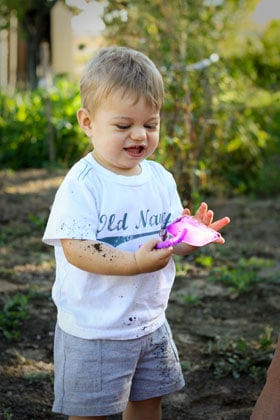 A little boy playing in dirt with a pink plastic shovel