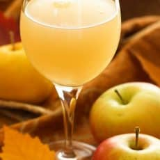 A wine glass with Russian apple kvas and full apples beside the glass