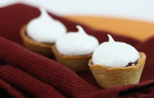 "Meringue and raspberry baskets ""korzinki"" on a red cloth napkin"