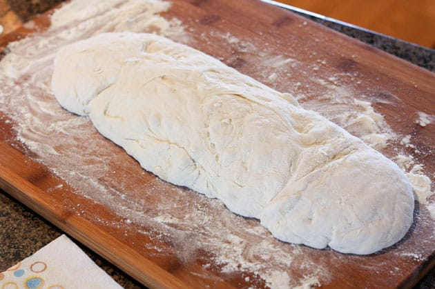 Dough shaped into a log on a floured, wooden cutting board