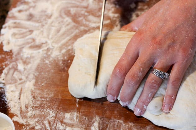 Dough being cut into small pieces on a floured cutting board