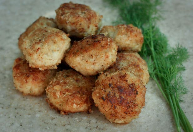 A close up of chicken and pork katleti, Russian meat patties, with dill beside them