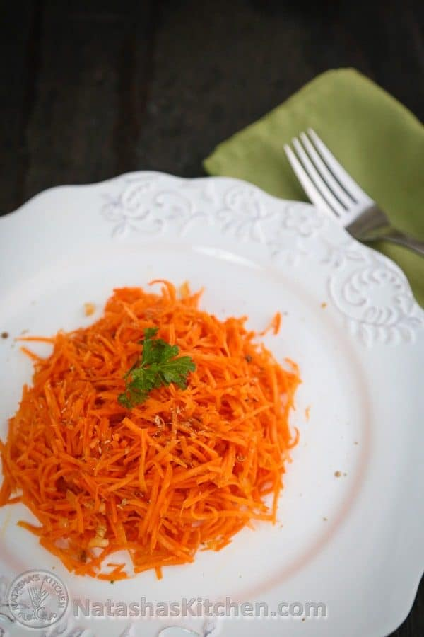 A white plate with carrot salad with coriander