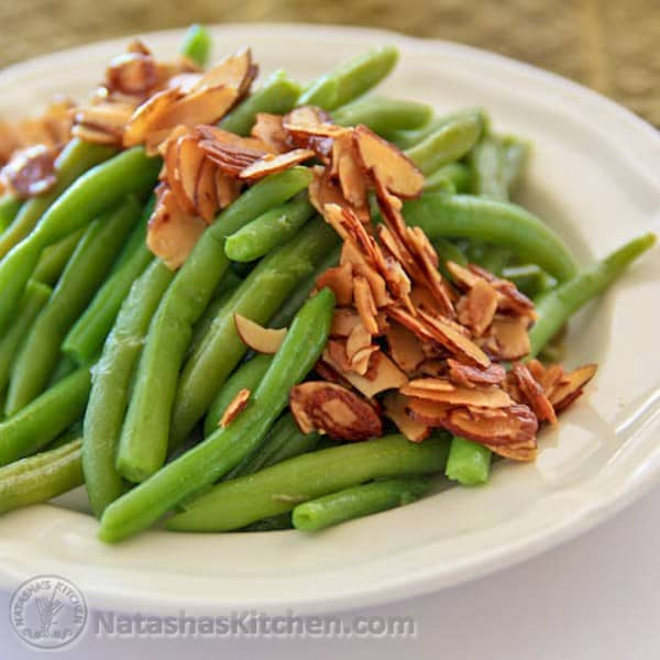 A white plate with green bean with almonds and butter