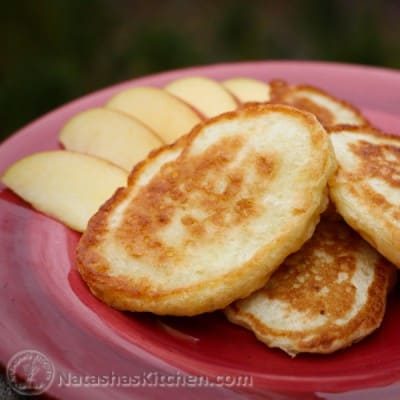 """These buttermilk pancakes are commonlyreferred to as """"oladi"""" but we called them """"blinchiki"""" growing up. They are loaded with diced apples. Yum!"""
