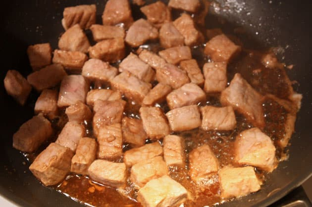 A pan with pork being browned