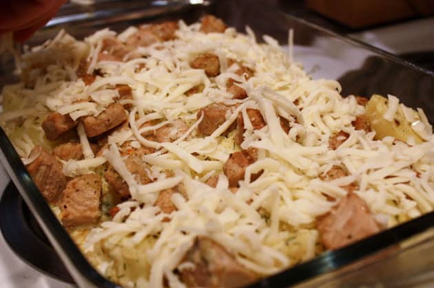 Cheese spread on pork and potato bake
