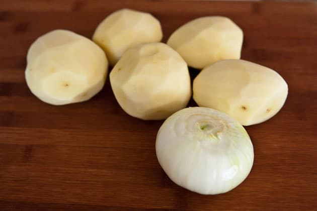 Five peeled potatoes and a peeled onion on a wooden cutting board