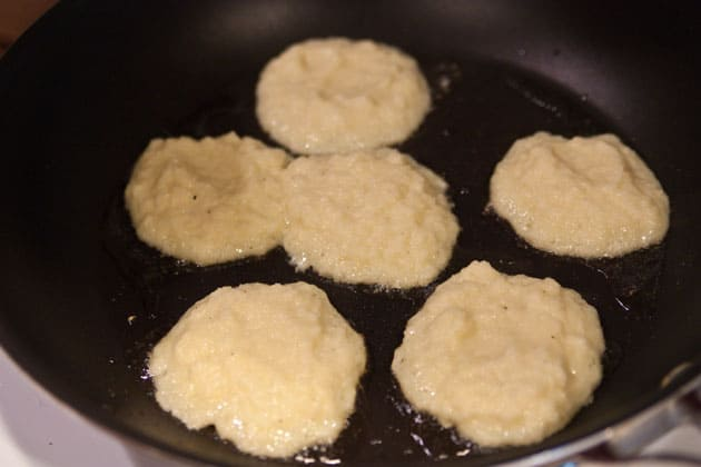 Potato pancakes being fried in a skillet