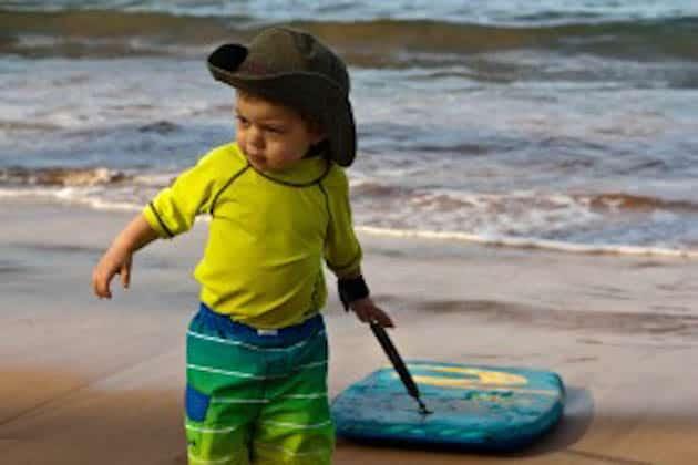 A little boy standing on a beach pulling a boogie board