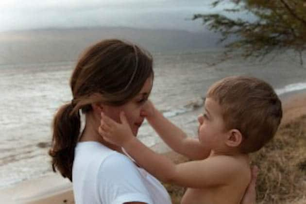 A woman standing on a beach holding her son while he grabs her cheeks