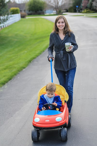 Natasha with her son in a toy car taking a walk