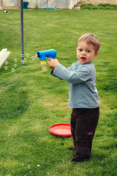 A little boy that is standing in the grass playing with a bubble machine