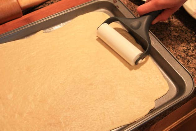 Pizza dough being rolled out on a baking pan