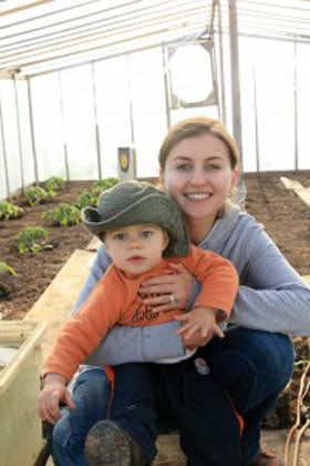 Natasha and her son in a green house