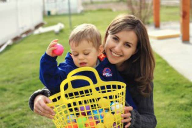 A little boy putting plastic Easter eggs in a basket with his mother