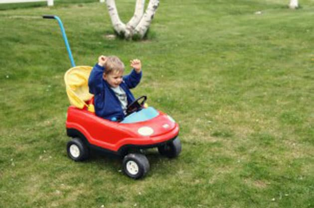 A little boy sitting in a toy car