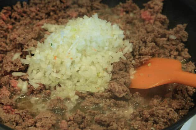 Diced onions added into a skillet with ground meat