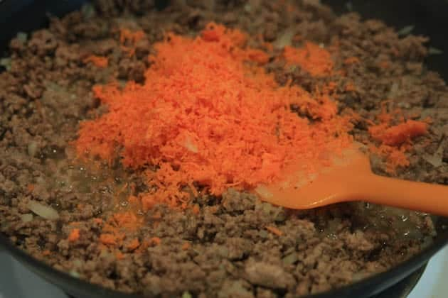 Shredded carrots added into skillet with ground meat and onions