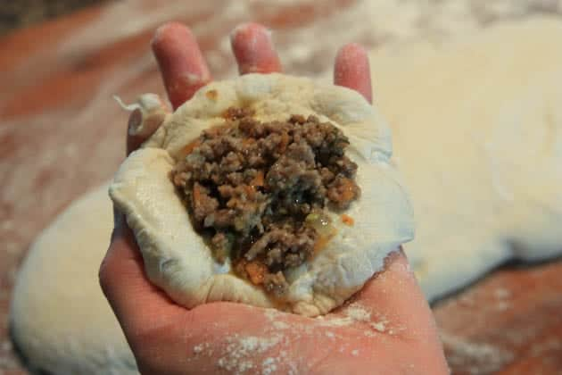 A circle of dough in someone\'s hand being filled with a meat filling