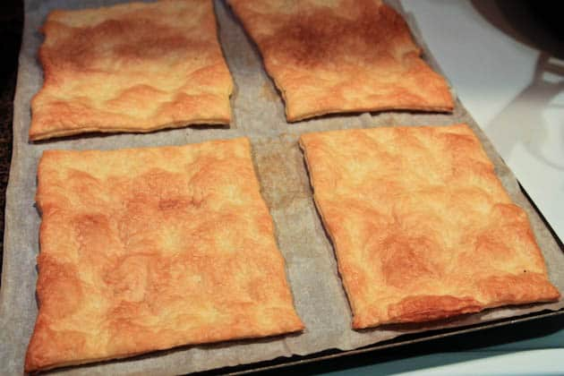 Four baked pieces of puff pastry on a baking pan