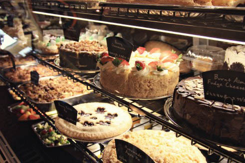 Different cakes, tarts and pies in a bakery display case