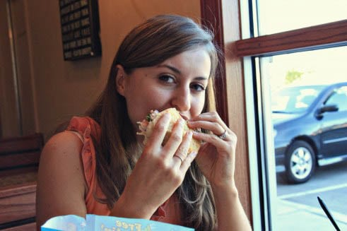 A woman sitting at a table eating a sandwich