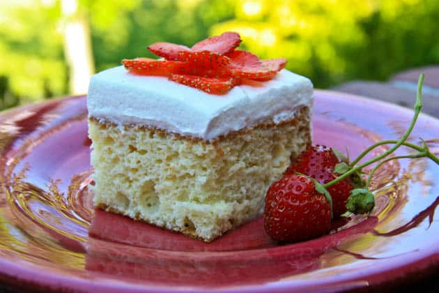 A slice of tres leches cake on a red plate