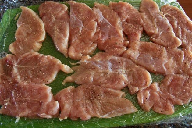 Seasoned chicken tenders on cutting board