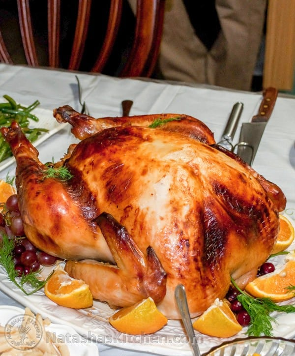 A large plate with a turkey garnished with oranges, grapes and dill