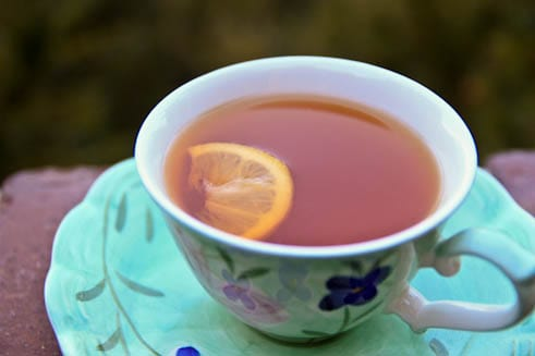 A close up of a tea with a slice of lemon in the cup