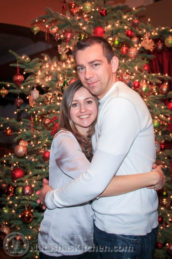 Natasha and her husband hugging with a Christmas tree behind them