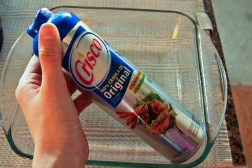 A spray can of Crisco being held above a glass baking dish