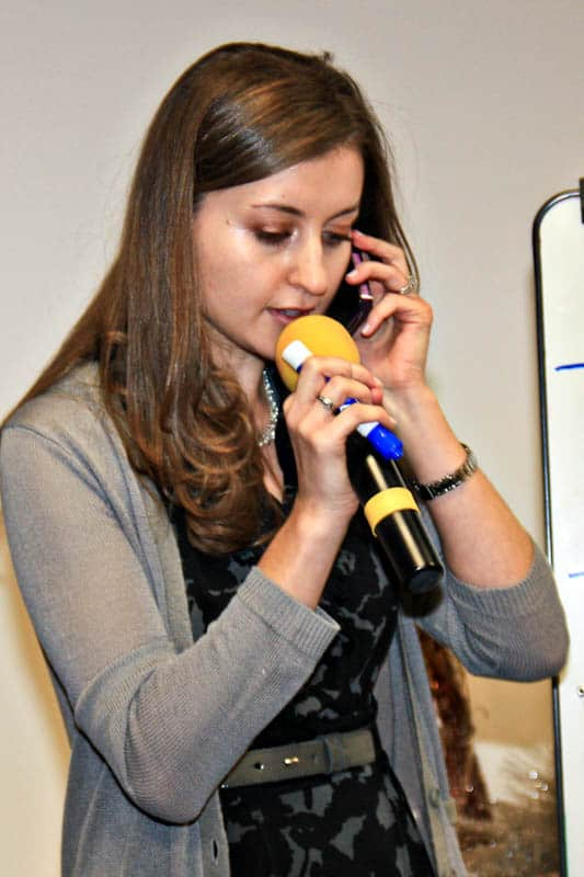 A woman holding a cell phone to her ear and a microphone in her other hand