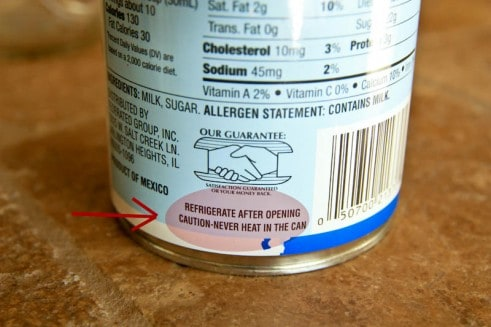A can with an arrow pointing at a label that says caution-never heat in the can