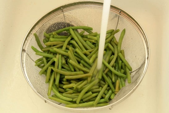 Green beens in a strainer being rinsed