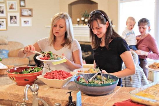 Women grabbing food into plates